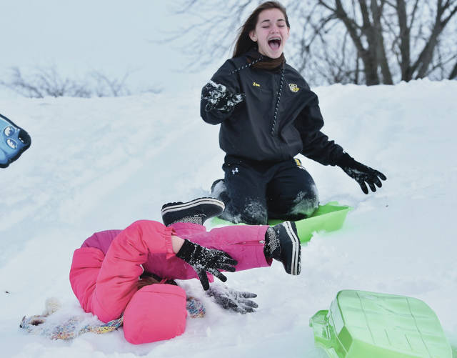 Aubree Frock, front, 8, daughter of Travis Frock and Amber Mayse, of Sidney, takes a tumble while sledding as Zoe Overholser, 14, daughter of Sherri and Mike Overholser, of Sidney, watches. Aubree was unhurt in the fall. Also sledding Tuesday, Jan. 22, was Aubree's brother, Anthony Frock, 10. The small hill is located along Main Avenue.