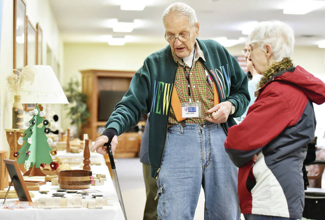 Paul Cook, left, talks to Doris Tangeman, both of Sidney, about his woodworking exhibit. Cook's woodworking was one of many exhibits at a hobby show at the Ohio Living Dorothy Love Amos Center. Stained glass, toy trains and paintings were some of the other hobbies on display. Cook uses the wood shop at Dorothy Love to do his woodworking.