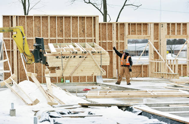 Tristin Stierley, of Leslie, Mich., guides a load of wood frames into place as the walls of the new Shelby County Animal Shelter being built on Gearhart Road began going up Thursday, Jan. 24.