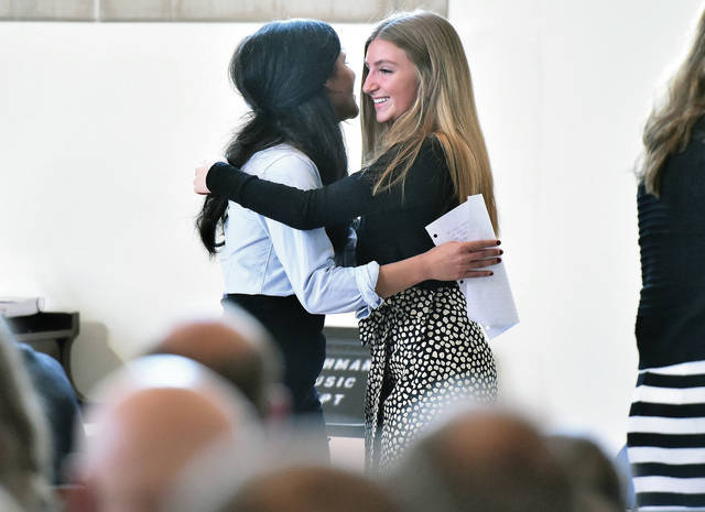 Kaila Sims, left, 18, daughter of Angela Foster, hugs Lisa Adams, 16, both of Sidney, daughter of John and Tara Adams, as Adams is inducted into the Lehman Catholic High School Honor Society during a ceremony Sunday, Jan. 27. Sims read a speech about why Adams was deserving of induction. Each Lehman student that was inducted had a friend or relative read a speech.