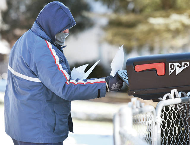 Sidney postal worker Cesar Maruffo, of Fort Loramie, had his nose and mouth covered as he delivered mail along Port Jefferson Road in sub zero temperatures Wednesday, Jan. 30.