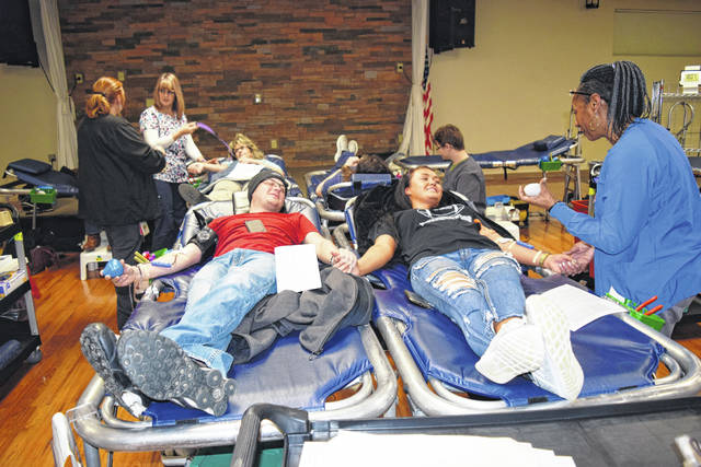 Cory Sherman, left, of Botkins, gives moral support to his friend, Haleigh Rhodus, by holding her hand as she donates blood during a recent memorial blood drive in Botkins.