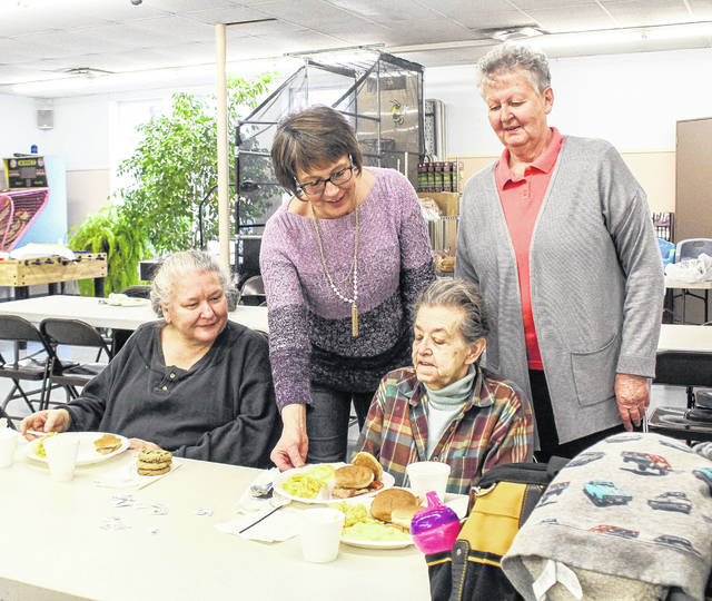 Holy Angels Soup Kitchen retiring Director Pat Luthman, standing right, watches as new Director Judy Smith, standing left, serves lunch to Roberta Beck, of Sidney, as Sharon Ross, of Sidney, looks on, at the Alpha Community Center, Monday, Jan. 14.