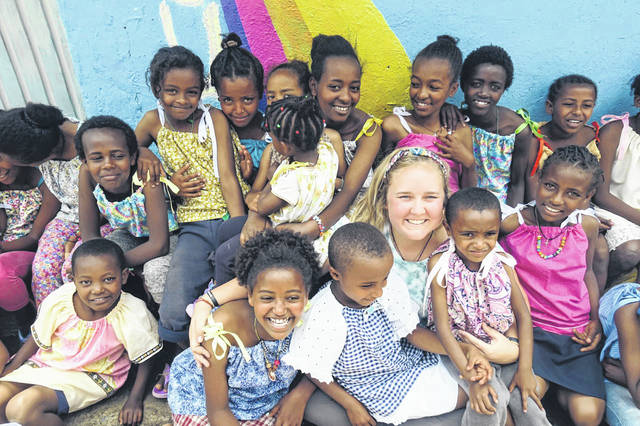 Sidney native Grace Frantz, center, is surrounded in Ehtopia by children wearing dresses made by volunteers in the Holy Angels Wrapped in Gods Love project.