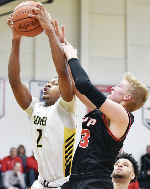 Sidney's Ratez Roberts comes down with a rebound while covered by Tippecanoe's Nolan Mader during a Greater Western Ohio Conference American North Division game on Tuesday in Sidney. Roberts scored 12 points.