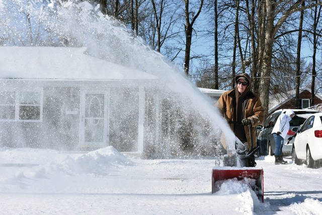 Rodney Hughes, of Sidney, clears his driveway of snow along Main Avenue, Sunday, Jan. 20.