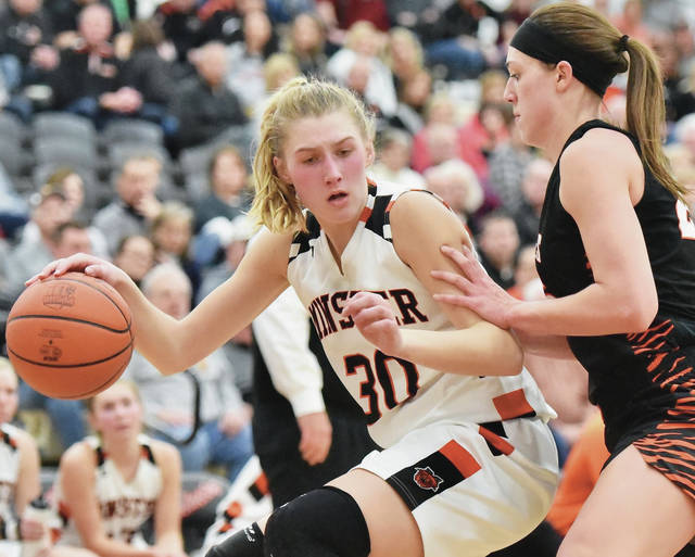 Minster's Courtney Prenger drives against Versailles' Lindsey Winner during a Midwest Athletic Conference game on Thursday in Minster. Prenger scored a season-high 27 points.