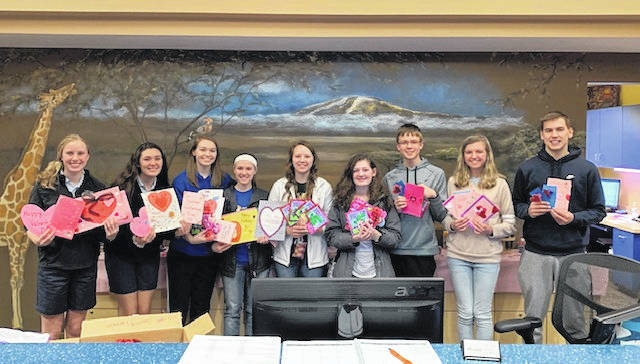 Members of the junior fair board hold some of the homemade Valentine cards, which will be delivered to local senior living homes ahead of Valentine's Day.