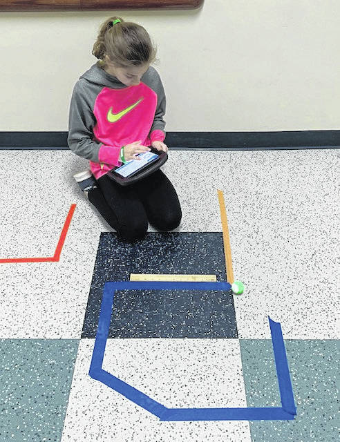 Russia fifth-grader Annabelle Armstrong, daughter of Melissa and Scott Armstrong, works to program her robot to complete the maze taped on the floor as part of the Manufacturing FUNdamentals program at Russia Local School on Valentine's Day.