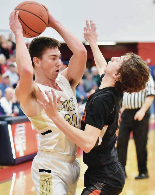 Botkins' Spencer Heuker looks to get past Ansonia's Matthew Farrier during a Division IV sectional semifinal on Tuesday at Piqua's Garbry Gymnasium. Heuker led all scorers with 19 points.