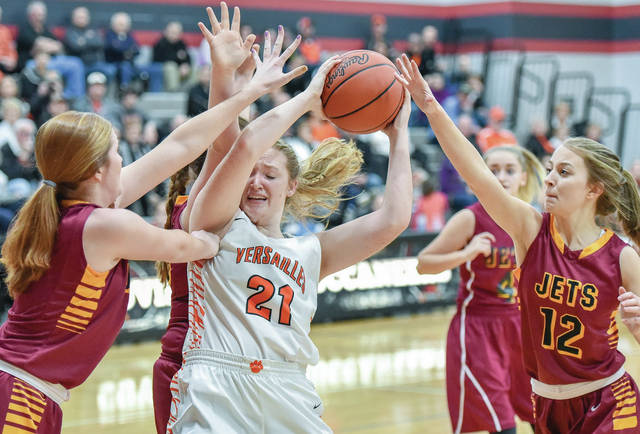 Versailles' Rachel Lyons battles Katie Baneck and Katelyn Dietrich for ball control during a Division III sectional semifinal on Thursday in Covington.