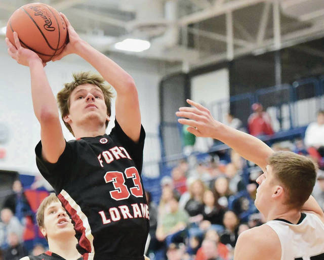 Fort Loramie's Eli Rosengarten shoots while covered by Covington's Gray Harshbarger during a Division IV sectional quarterfinal on Friday at Garbry Gymnasium in Piqua. Rosengarten scored 15 points in the first half to help the Redskins earn a big win.