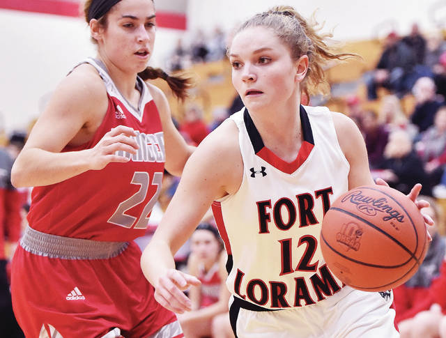 Fort Loramie's Kennedi Gephart dribbles past New Knoxville's Erin Scott during a nonconference game in Fort Loramie on Dec. 27.
