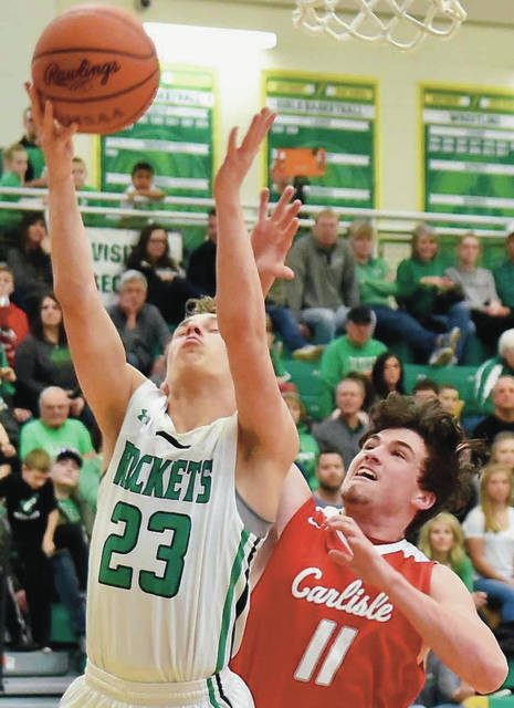 Anna junior guard Bart Bixler shoots as Carlisle's Logan Gross defends during a Division III sectional opener against Carlisle on Saturday at Northmont.