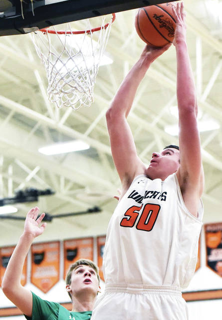 Minster's Jarod Schulze shoots as Anna's Griffin Doseck defends during a nonconference game on Saturday in Minster.