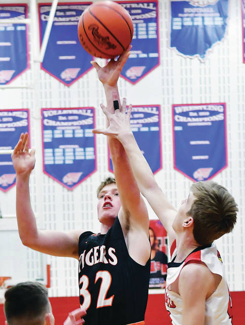 Jackson Center's Aidan Reichert shoots with pressure from Triad's Jacob Simonelli during a Division IV sectional opener on Saturday at Piqua's Garbry Gymnasium.