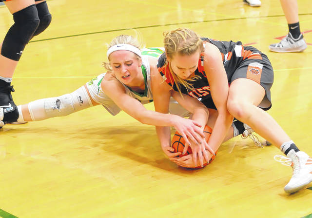 Ottoville's Quinley Schlagbaum, left, goes to the floor with Minster's Jessica Falk for a loose ballduring a nonconference game on Monday in Ottoville.