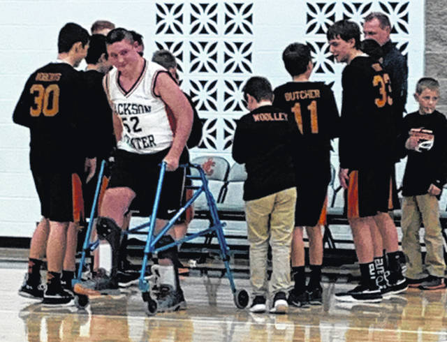 Landon Reese, in white, with teammates during the Jackson Center Tigers' final regular season basketball game of his eighth-grade year on Jan. 28. Reese was seriously injured after he was kicked in the head by a horse in 2012 and regularly works to recover from the incident. He was given the opportunity to start for his team against the Fairlawn Jets.
