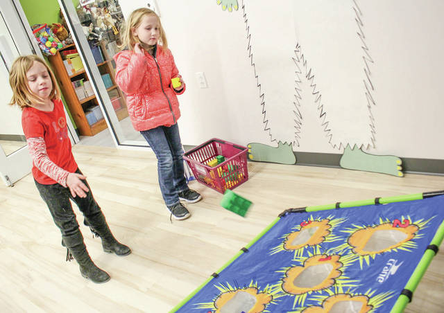 Sisters Kinsey Briley, left, 7, and Cailin Briley, 9, both of sidney, daughters of Landra Green, play at the Amos Memorial Library Monday, Jan. 28. The library had a LEGO day. Kids could come play games and do activities at the event.