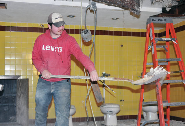 Westerheide Construction employee Devin Kuch, of Bellefontaine, shovels floor tiles and plaster in the upstairs women's bathroom of the Historic Sidney Theatre, recently. The current phase of renovating the old theater remodeling the two upstairs and two downstairs bathrooms.