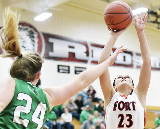 Fort Loramie's Taylor Ratermann shoots with pressure from Anna's Kiplyn Rowland during a Shelby County Athletic League game on Saturday in Fort Loramie. The Redskins are No. 1 in Division IV again this week.
