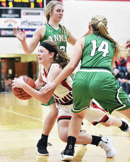 Fort Loramie's McKenna Mannier goes down while pressured by Anna's Mary Landis and Breah Kuck during a Shelby County Athletic League game on Saturday in Fort Loramie.