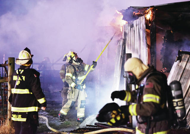 Firefighters tear apart what is left of the barn to reach hot spots.