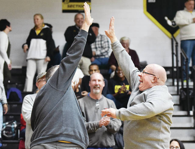 Dave Ross, left, of Fort Loramie, gives Lehman Catholic baseball coach and Sidney Middle School girls basketball coach Dave King a very high five after King was recognized for being inducted into the Ohio Baseball Coaches Association Hall of Fame. King also made three ceremonial basketball shots to earn a donation of $30,000 for a new indoor complex at Sidney High School. King was recognized during halftime of the Sidney and Lehman Catholic boys basketball game at Sidney Monday.