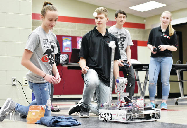 Fort Loramie High School Robotics Club members, left to right, Anna Detrick, 14, daughter of Dustin Detrick, Jacob Sherman, 15, daughter of Jenny and Matt Sherman, Isaiah Scheer, 15, son of James and Kalee Scheer, and Lauren Bergman, 15, all of Fort Loramie, daughter of Keith and Amy Bergman, demonstrate one of their robots which launches pinpong balls. The club members held the demonstration in the Fort Loramie High School cafeteria during Fort Loramie boys home basketball games Tuesday, Feb. 5.