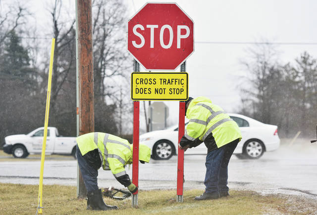 Shelby County Highway Department employees Zach Hill, left, of Sidney, and Myron Gaier, of Fort Loramie, install a new stop sign at the intersection of Mason Road and County Road 25A. The two men stood in the pouring rain Thursday, Feb. 7, to replace a stop sign that had been knocked over by a semi trailer. The rain made for lots of flooded farm fields and a high fast waters in area creeks.