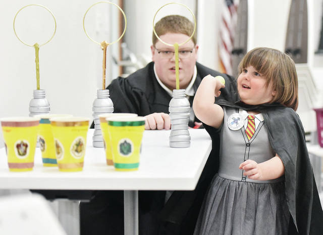 Calliope Kimbler, right, 3, of Sidney, daughter of Danny and Betsy Kimbler plays the game of Quidditch as Bob Jones, of Lima, watches. Quidditch was one of the many Harry Potter themed games that kids took part in during Harry Potter Night at the Amos Memorial Public Library Thursday, Feb. 7.