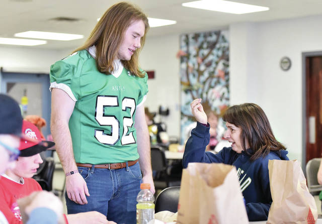 S & H Products associate Lesli Davis, right, of Sidney, asks Anna High School varsity football player Isaac Dodds, 18, of Anna, son of Dan and Jayma Dodds, if he got hit in the head a lot playing football. Dodds and several other Anna High School athletes visited with S & H Products associates during lunch Friday, Feb. 8.