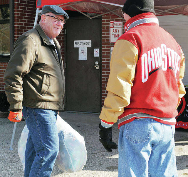 Bill Ankney, left, brings a bag of cans to SCARF board member Bob Baird, both of Sidney, to donate to SCARF during a Cans for Canines fundraiser Saturday, Feb. 9. Money raised will be matched by The Styling Company up to $250.