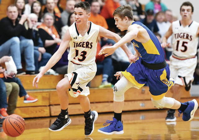 Jackson Center's Christopher Elchert dribbles with pressure from Marion Local's Alex Eyink during a nonconference game on Monday in Jackson Center.