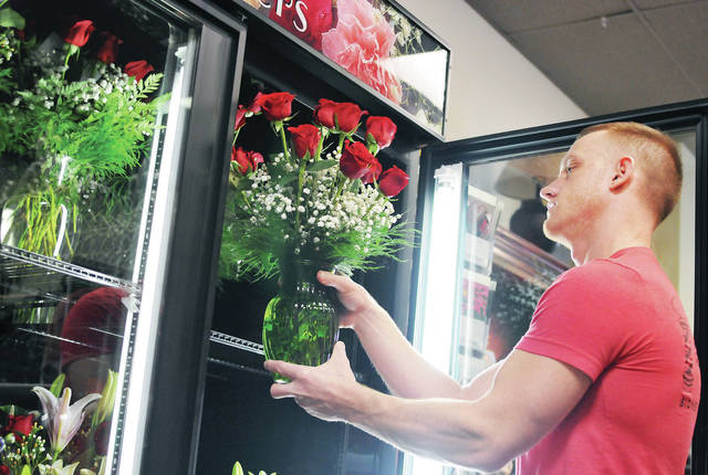 "Mark Evans, of Troy, looks over a Valentine's Day flower arrangement at The Ivy Garland Wednesday, Feb. 13. The Ivy Garland owner Cindy Garland says that flower sales are up this year and that ""people are buying other gift items to go with the flowers."""