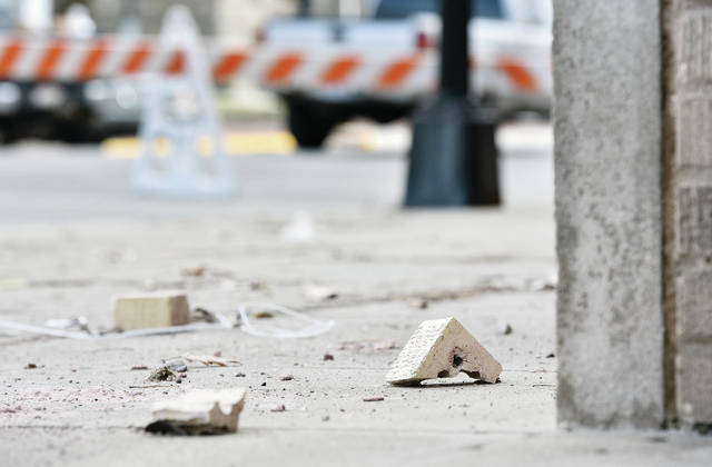 "Pieces of brick lie on the sidewalk in front of the Ohio Building, along Ohio Avenue in Sidney, Friday, Feb. 15. They fell from the parapet, Thursday. Behind the bricks are orange-striped blockades surrounding the front of the building to keep people off the sidewalk. City workers will begin to replace the roof on the building next week. Assistant City Manager/Public Works Director Gary Clough said the barricades will remain in place for ""a couple of months"" until roof work is complete."