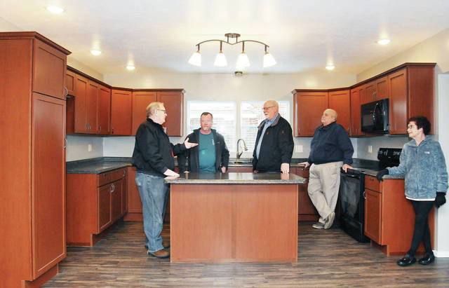 Jeff Wood, second from left, of Sidney, talks with, left to right, Land Bank board member Dave Voisard, of Sidney, Land Bank Director Douglas Ahlers, of Fort Loramie, Land Bank board member John Coffield and former Land Bank board member Linda Meininger, both of Sidney, in the kitchen of the house Wood has rebuilt along Foraker Avenue, recently. Wood gave the board a tour of the home.