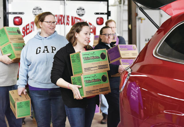 Loading Girl Scout cookies into a SUV at the EMA Building at the Shelby County Fairgrounds are, left to right, Cassie Oakes, of Wapakoneta, Kim Leopold and Michele Jones, both of Anna, and Mike Keiser, of Sidney. This batch of cookies will be sold by Sidney Girl Scout Junior Troop 20319. Kerry Kieiser is the scout leader. This year 2,456 cases were sold. Booth sales will begin Friday, March 1.
