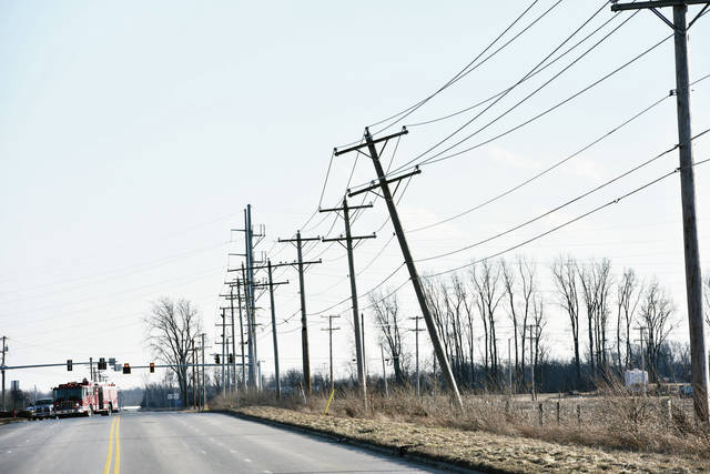 A utility pole dangles next to S. Vandemark Road around 5 pm. The pole broke during the wind storm Sunday Feb. 24. The Sidney Police and Sidney Fire Department blocked off the street.
