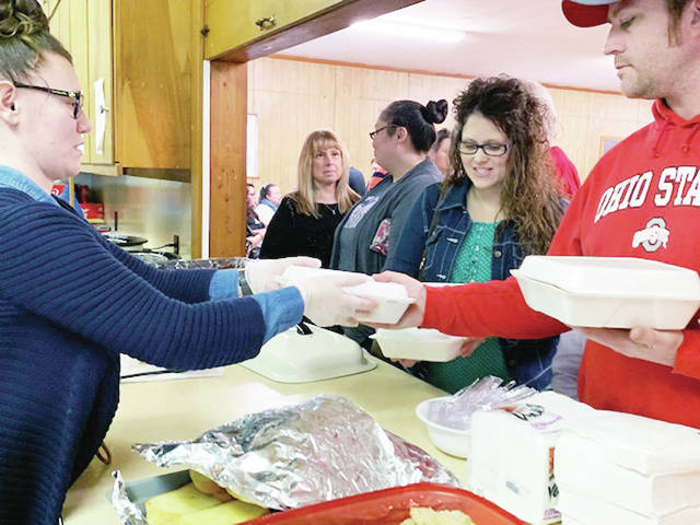 Tiffany Beaver, left, of Sidney, hands a spaghetti dinner to go to Mike Coy and his Wife Deanna, from Houston, during a benefit for Grage Couch, of Sidney. The brought in around $3300. The benefit was held at the Hardin United Methodist Church Saturday, Feb. 23. Couch is now on a transplant list for new lungs.