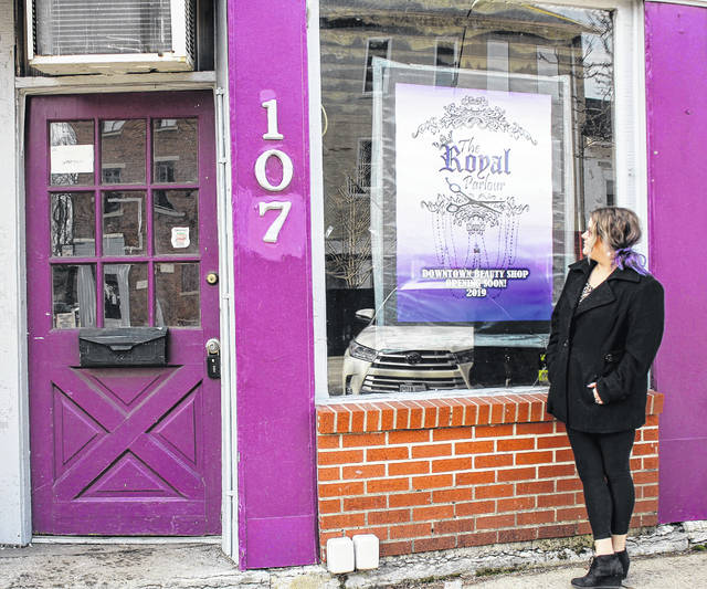Allison Marlow, of Quincy, admires the sign announcing the upcoming opening of her new beauty salon in downtown Sidney. Marlow was at the site, where renovations are ongoing, Tuesday, Feb. 19.