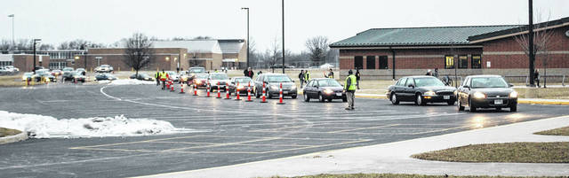 A line of cars drives through the pylons at Sidney Middle School Thursday morning as students are dropped off for school. A new traffic pattern for both Sidney High School and Sidney Middle School in preparation or the rehabilitation of the Fair Road bridge.