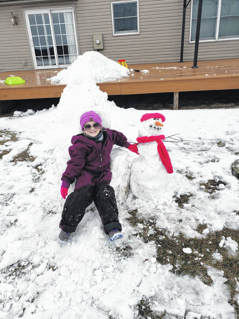 Alexis Burton, 6, daughter of Dustin and Kelly Burton, enjoys the snow Saturday before it all melted Sunday and Monday. Alexis made a snowman, while her dad made her a snow chair to sit on.