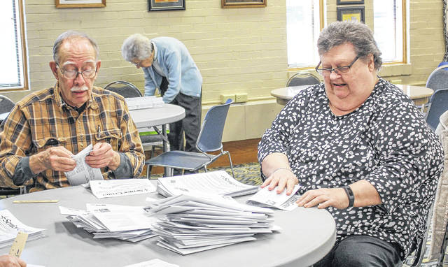 Eileen Wiseman, right, retiring executive director of the Senior Center of Sidney and Shelby County, prepares the center's monthly newsletter for mailing with Andy Huff, left, and Farrel Kaplan, both of Sidney, Monday, Feb. 25. The center will host an open house in Wiseman's honor, Friday, March 1, from 4 to 7 p.m.