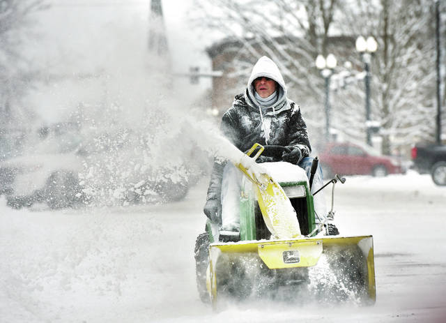 Amos Memorial Public Library employee Rick Langhorst, of Sidney, uses a riding snow blower to clear snow along Norh Main Avenue next to the library, Friday, Feb. 1.