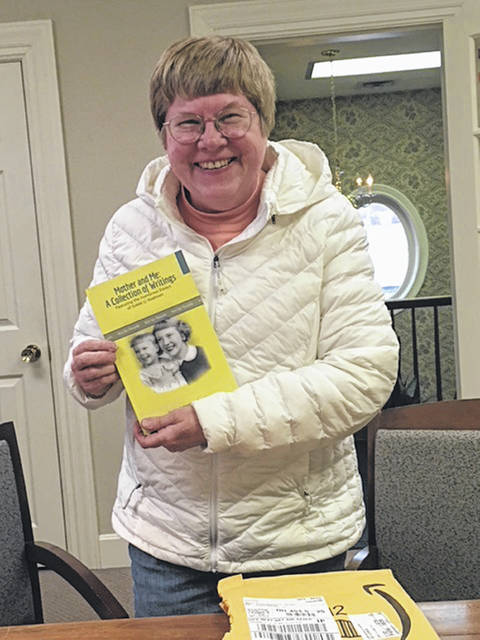 "Elaine Schweller-Snyder, of Sidney, can't contain her enthusiasm as she shows the proof copy, fresh from the publisher, of her book, ""Mother and Me: A Collection of Writings,"" in the offices of Creative Marketing Strategies in Sidney in December."