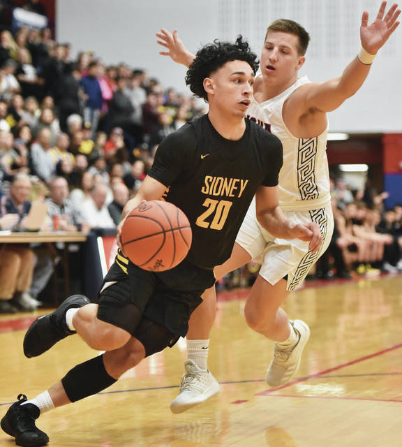 Sidney's Andre Gordon drives past Piqua's Mick Karn during a Greater Western Ohio Conference American North Division game on Friday in Piqua. The Yellow Jackets were voted the No. 4 seed in the Dayton Div. I sectional.