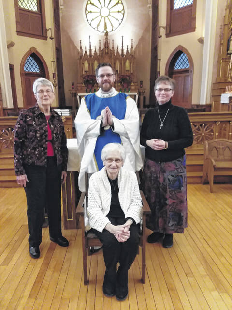 The Rev. Alex Witt, center, is shown with seamstresses Mary Honigford, left to right, Ann Will (seated) and Kathy Homan, who made the new vestments. Not pictured is Jerry Will and McKenna Gels.
