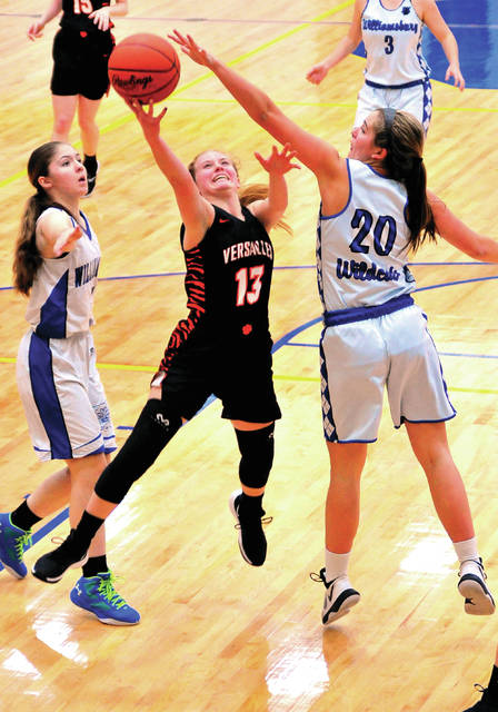 Versailles' Caitlin McEldowney shoots between Williamsburg's Emily Hart, left, and Paige Fisher during a Division III district final on Saturday om Springfield.