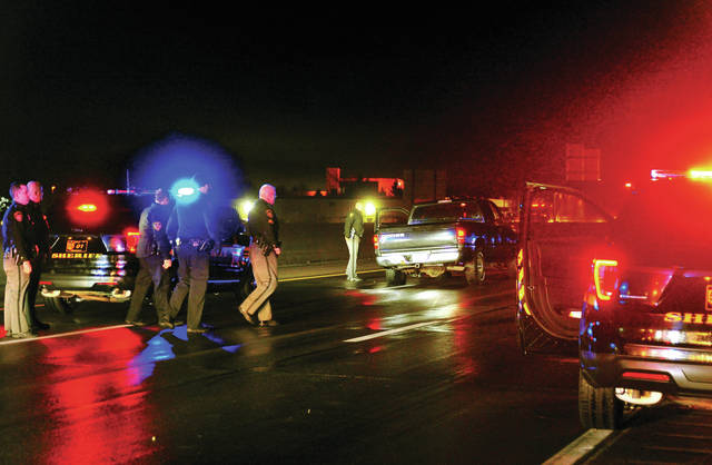 Law enforcement officers from several agencies regroup after the arrest of a suspect involved in a chase through Shelby and Miami Counties on Saturday evening. The chase ended on southbound Interstate 75 near the 73-mile marker when officers spiked the tires of the fleeing pickup.